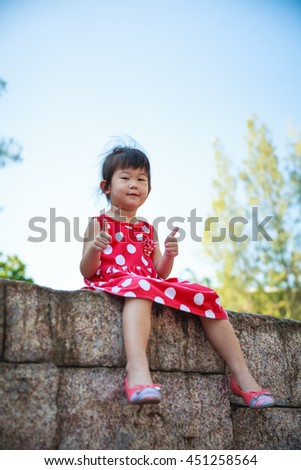 Happy asian girl with thump up and looking at camera at park. Child relaxing outdoors in the day time, travel on vacation. Positive human emotion. - stock photo