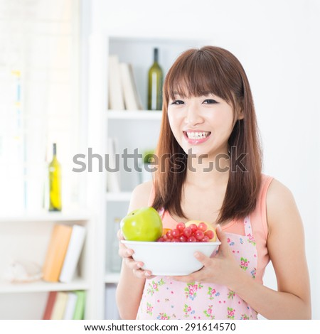 Happy Asian housewife with apron holding a bowl of fresh fruits. Young woman indoors living lifestyle at home. - stock photo