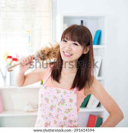Happy Asian housewife with apron housekeeping, hand holding a duster and smiling. Young woman indoors living lifestyle at home. - stock photo