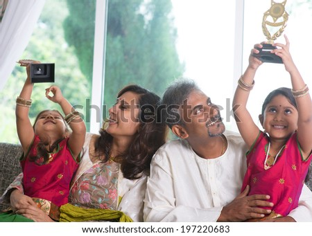 Happy Asian Indian family at home. Kid raised their trophy high up, education achievement concept. Parents and children indoor lifestyle.