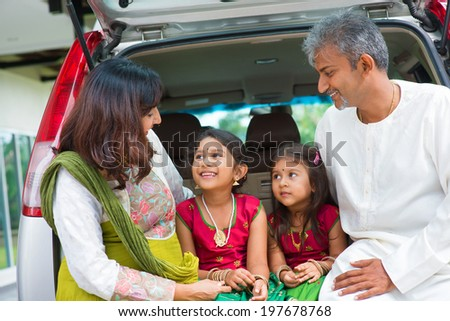 Happy Asian Indian family sitting in car talking and smiling happily, ready to summer vacation. - stock photo