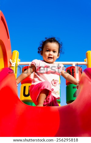 happy asian infant playing at playground during sunny day - stock photo