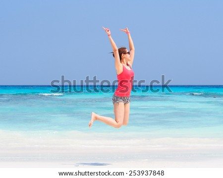 happy Asian lady jumping at a beautiful beach in Thailand - stock photo