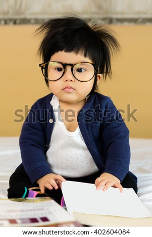 Happy asian little girl 7 month with big book wearing  glasses, Baby geniuses concept. - stock photo