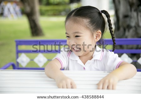 Happy asian little girl sitting on the swing in playground outdoors