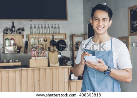 Happy asian male waiter in apron writing order and looking at camera