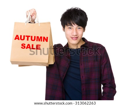 Happy Asian man shopper holding shopping bag for showing phrase of autumn sale