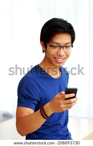Happy asian man using smartphone at home - stock photo