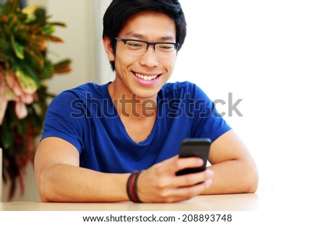Happy asian man using smartphone at home
