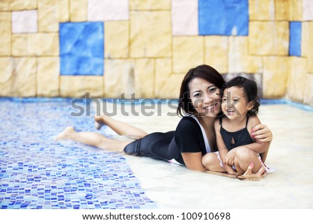 Happy asian mother and daughter posing at swimming pool