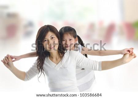 Happy Asian mother piggyback ride daughter indoor - stock photo