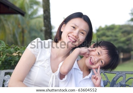Happy asian mother playing with son