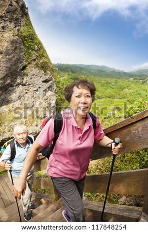 happy asian senior couple hiking in the mountain - stock photo