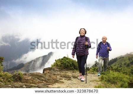 happy asian senior couple hiking on the mountain - stock photo