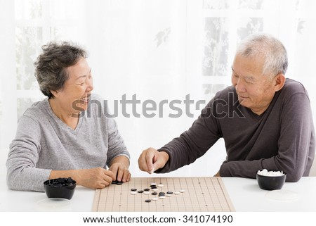 happy asian senior couple playing chess in living room - stock photo