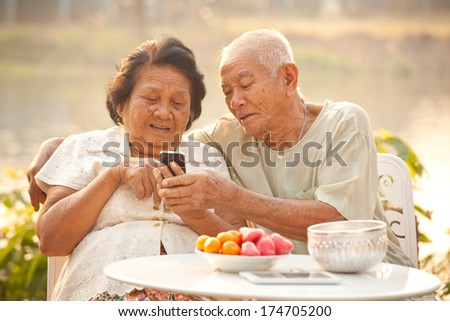 Happy asian senior couple using the mobile phone on outdoor background - stock photo