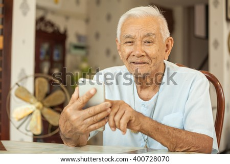 Happy asian senior man using the mobile phone at home - stock photo