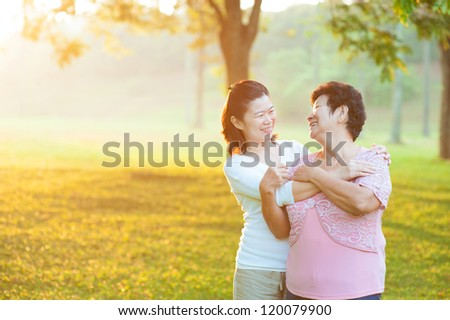 Happy Asian senior mother with her daughter at outdoor park - stock photo