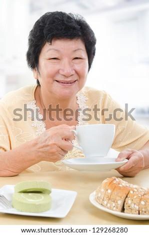 Happy Asian senior woman having breakfast at home - stock photo