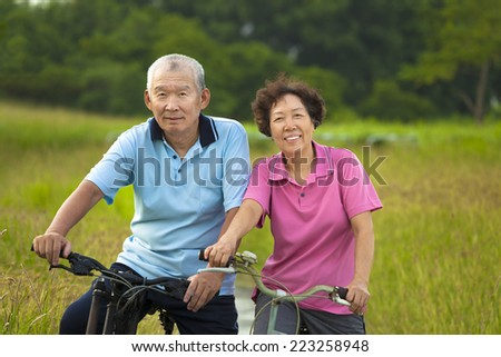 Happy Asian seniors couple biking in Park. retirement and health concept - stock photo