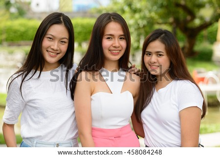 Happy Asian teenagers friends smiling outdoors - stock photo