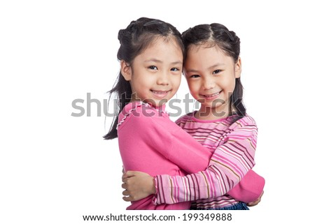 Happy  Asian twin sisters hug each other