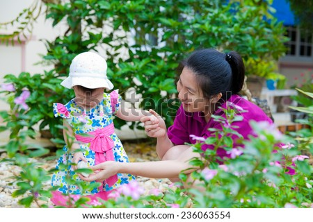 Happy asian woman and little girl relaxing at home back yard and sun light in holiday - stock photo
