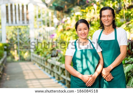 Happy Asian woman and man in aprons looking at camera in greenhouse - stock photo