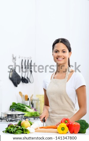 Happy asian woman cooking, slicing and preparing food in the kitchen wearing a apron - stock photo