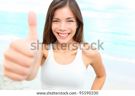 Happy asian woman giving thumbs up success hand sign outside on beach smiling joyful. Sporty fit young mixed race Chinese Asian Caucasian female fitness model outdoors. - stock photo