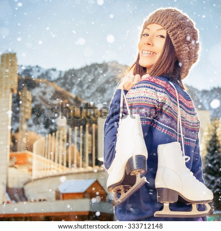 Happy asian woman going to ice skating outdoor. She dressed in pullover and warm hat. Holding skates shoes. Healthy lifestyle and sport concept at olympic stadium. Winter weather with snowy blizzard - stock photo