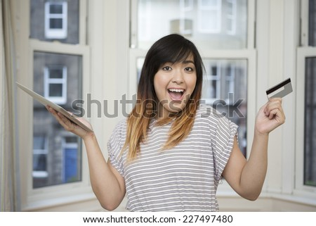 Happy Asian woman holding Tablet device and credit card. Concept about internet shopping. Looking at the camera. - stock photo