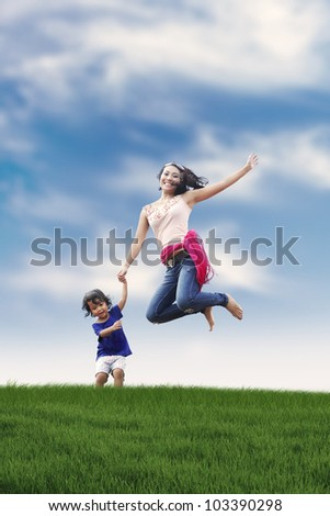 Happy asian woman jumping with her daughter shot outdoor - stock photo