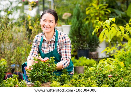 Happy Asian woman looking at camera in the garden - stock photo