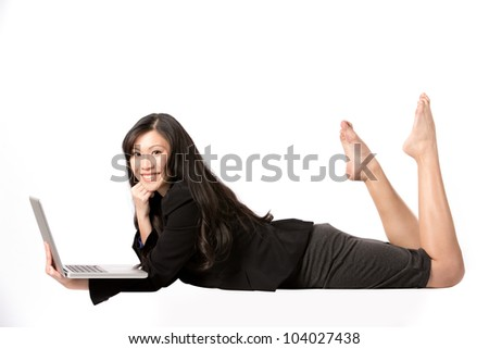 Happy Asian Woman lying down using a laptop. - stock photo