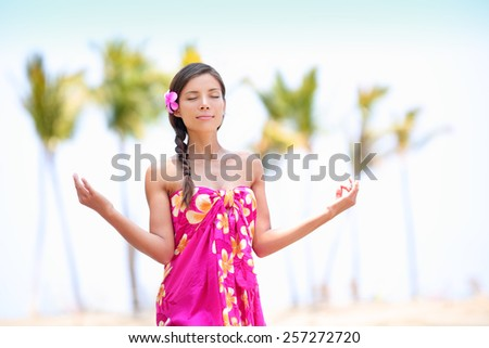 Happy Asian woman meditating on Hawaiian palm beach in sarong, hands up. Beautiful mixed race female model enjoying sun in worship and meditation zen. Big Island, Hawaii, USA. - stock photo