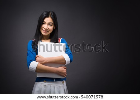 Happy Asian woman posing with blank poster or white notebook for writing any ideas and emotions in studio.