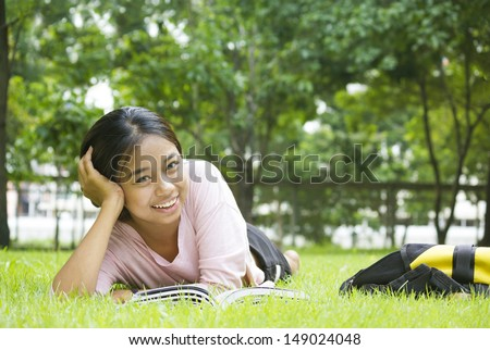 Happy Asian woman reading book while lying on lawn