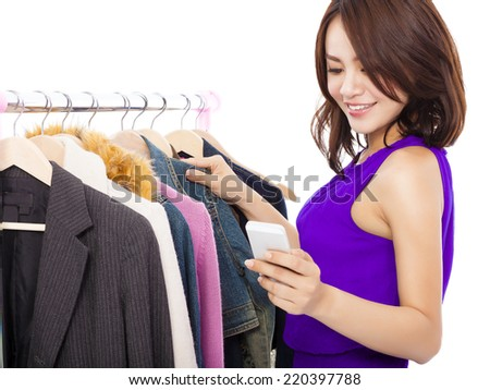 Happy asian Woman shopping clothes with a mobile phone over white background - stock photo