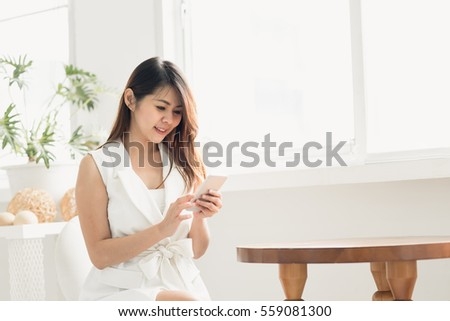 Happy Asian woman smiling while using smart phone in white room