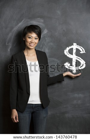 Happy Asian woman standing in front of dollar sign written on a chalkboard. - stock photo