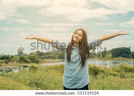 Happy asian woman with opened arms outdoors enjoy her freedom and leave space for adding your content. background look old or vintage style. (vintage color tone)