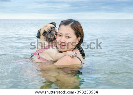 Happy Asian women girl hug play immersed in beach sea water with cute dog puppy pug in weekend holiday - stock photo