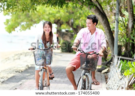 Happy asian young couple riding bicycle laughing together - stock photo