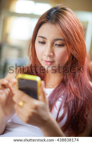 Happy asian young woman lying using smart phone at home