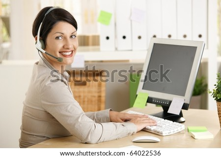 Happy assistant talking on headset, typing on computer in office.?