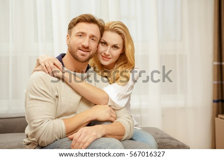 Happy at home. Beautiful mature woman embracing her handsome husband relaxing together at their new home on the sofa copyspace home family love couple relationships happiness coziness comfort concept