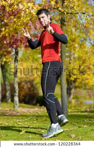Happy athlete running and winning. Success and victory in sport. Male runner doing victory symbol. - stock photo