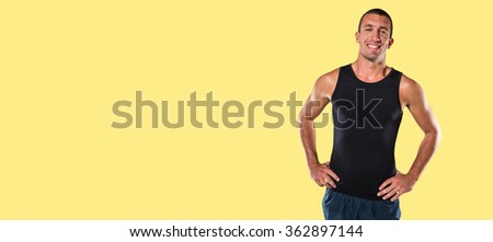 Happy athlete with hands on hip standing against yellow background