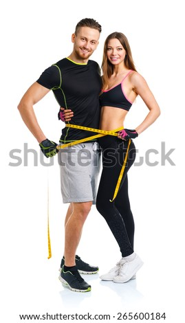 Happy athletic couple - man and woman with measuring tape on the white background - stock photo